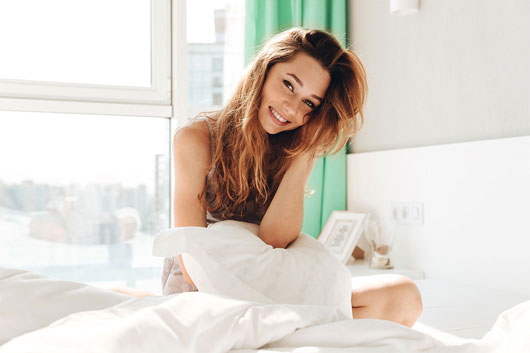 Woman smiling in bed next to the window