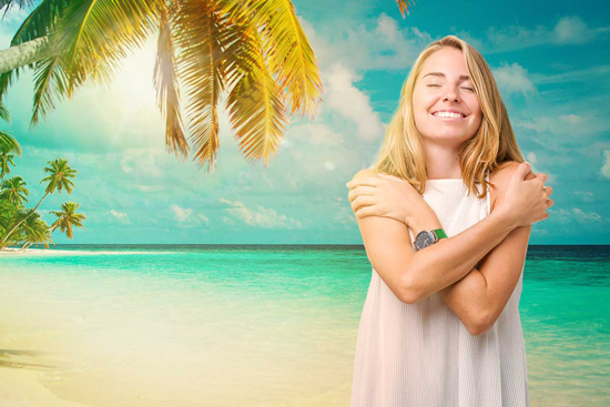 Woman in white standing on the beach smiling
