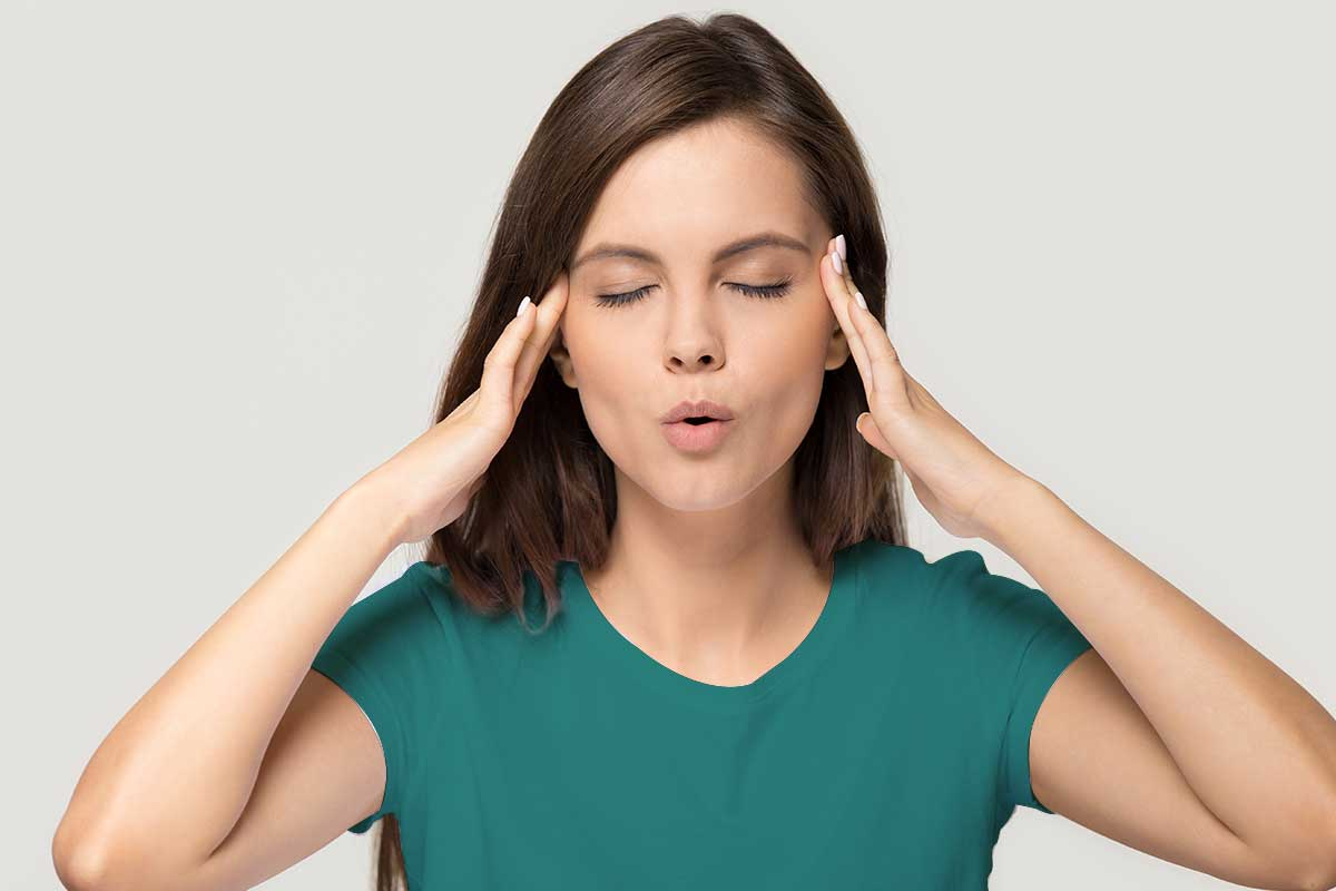 Woman in a green shirt with hands on her forehead expressing a headache