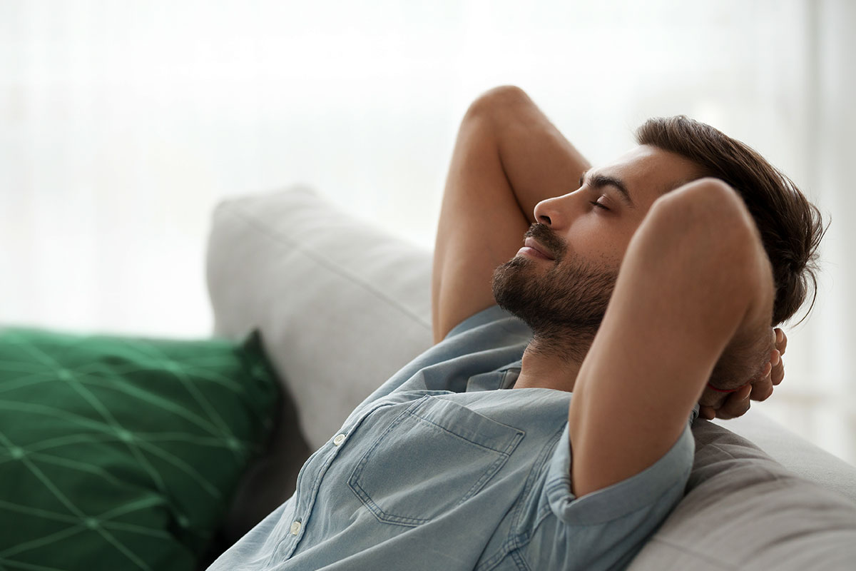 A man in light blue cotton shirt relaxing on the couch with closed eyes