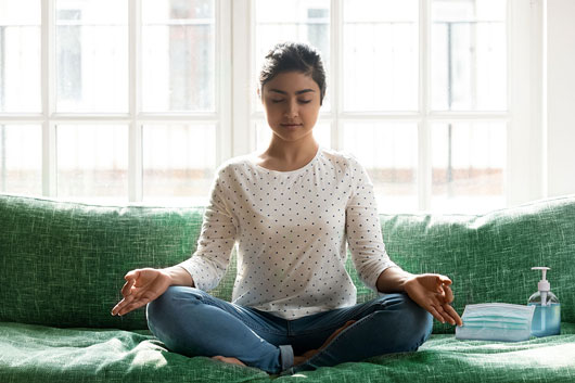 Woman sitting on the couch with eyes closed and meditating