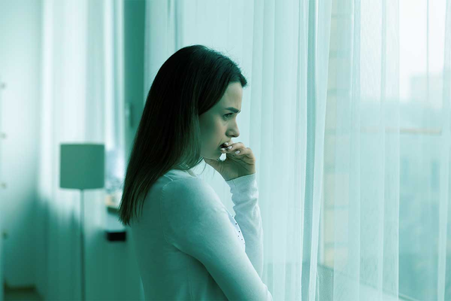 Worried woman in white looking out the window