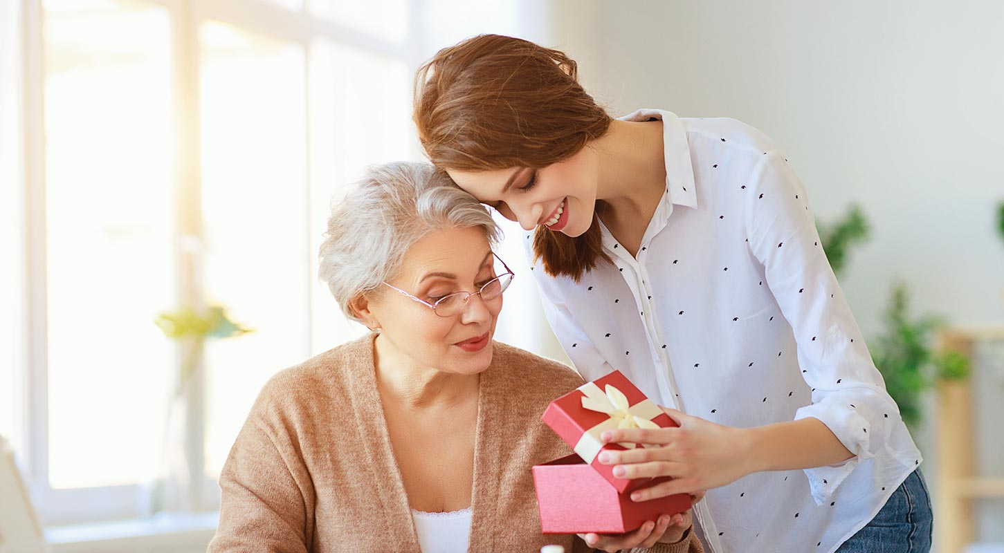 A woman giving her elderly mother a gift