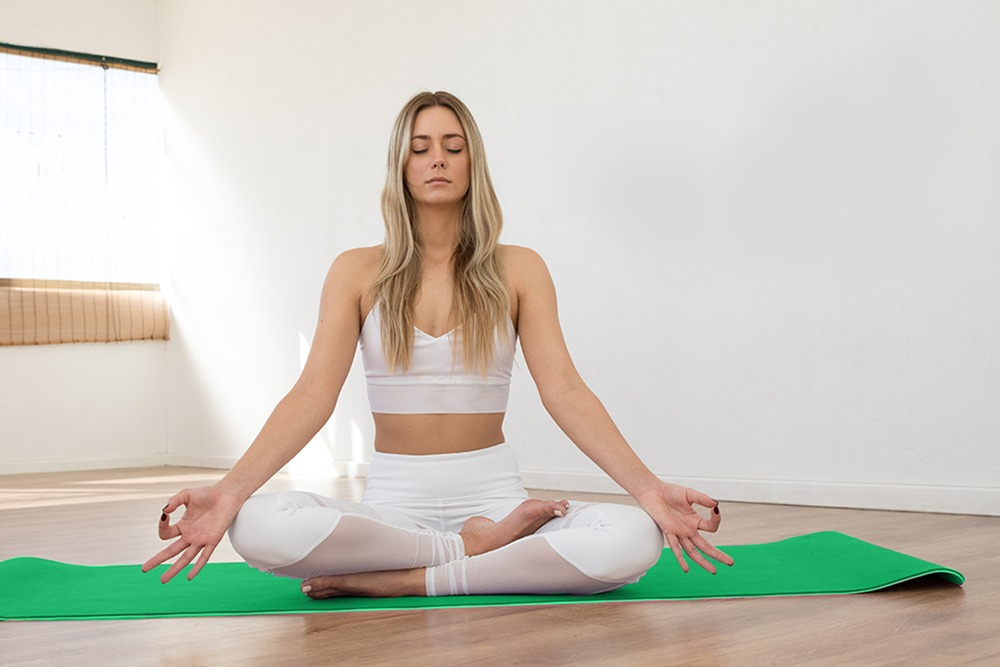 A woman wearing white, blonde hair is sitting on a bright green yoga mat in a meditative state. The background is a white wall with a window on left side from where there is light coming in. The floor is wooden