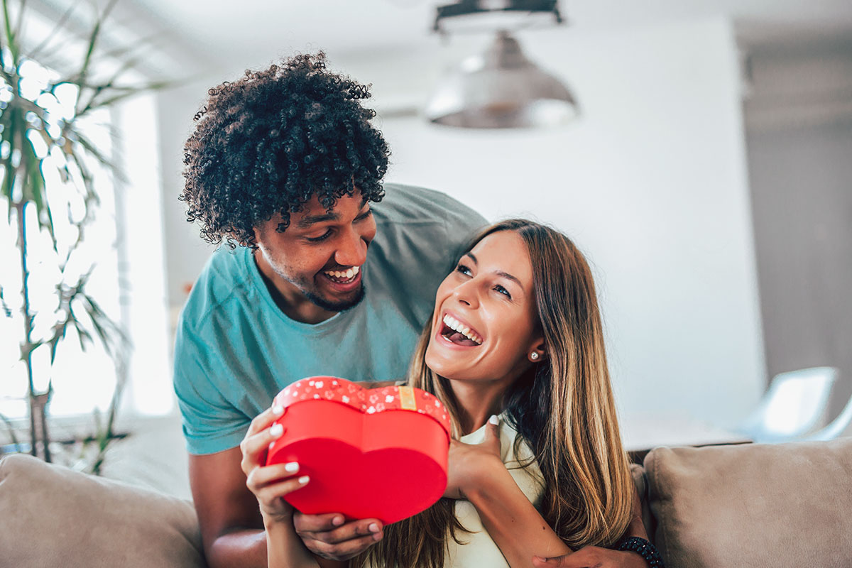 A man giving a woman a red, heart-shaped gift box